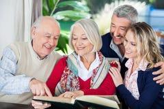 Nietos felices con el libro de lectura de los abuelos Imagen de archivo libre de regalías