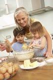 Nietos que ayudan a la abuela a cocer las tortas en cocina Foto de archivo