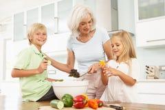 Nietos que ayudan a la abuela a preparar la ensalada fotos de archivo