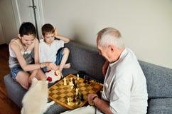 Nietos sonrientes con el abuelo que juega a ajedrez y que lo mira Foto de archivo libre de regalías