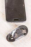 Nieużywany czerni usb kabel z telefonem komórkowym w tle Zdjęcia Stock