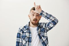 Nieudacznik jest przeznaczeniem Przystojny młody europejski brat w błękitnym prostym koszulowym seansie gubi gest nad czołem, wyś fotografia stock