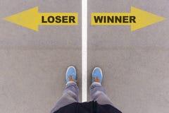 Nieudacznik vs zwycięzcy teksta strzała na asfalt ziemi, ciekach i butach dalej, obraz stock