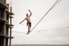Nieustraszenie mężczyzna równoważenie na slackline wysokości przeciw pustemu budynkowi i niebu obraz royalty free