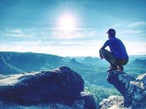 Nieustraszenie mężczyzna w sportswear obsiadaniu na falezy krawędzi i patrzeć daleki horyzont fotografia stock