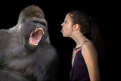 Nieustraszenie młoda dziewczyna z gniewnym gorylem zdjęcia stock