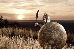 Nieustraszenie młody Spartański wojownik pozuje w polu zdjęcie royalty free