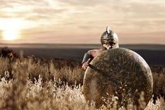 Nieustraszenie młody Spartański wojownik pozuje w polu zdjęcie stock