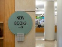Nieuw boekenteken die aan het recht met bibliotheek op achtergrond richten stock afbeeldingen