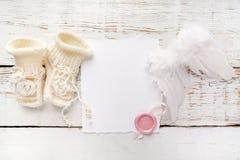 Nieuw - de geboren of Kaart van de doopselgroet Spatie met de schoenen van het babymeisje en engelenvleugels op witte houten acht stock afbeeldingen