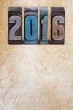 Nieuw de prentbriefkaarmalplaatje van de jaarviering 2016 geschreven met gekleurd uitstekend letterzetsel Oude Witboekachtergrond Stock Afbeelding