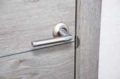 Nieuw deurhandvat op de nieuwe deur stock foto