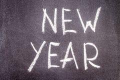 Nieuw die jaar met krijt op een zwarte achtergrond wordt geschreven Stock Foto's