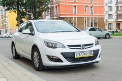 Nieuw die Opel Astra dichtbij moderne huizen in suburbia wordt geparkeerd Royalty-vrije Stock Fotografie