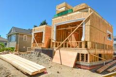 Nieuw familiehuis in aanbouw met stapels 2x4-houtraad op de bovenkant stock fotografie