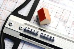 Nieuw huisproject met de tekst van het droomhuis op heerser Architectuurplan en klein modelhuis Royalty-vrije Stock Afbeeldingen