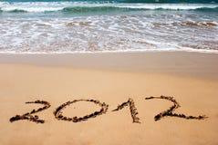 Nieuw jaar 2012 op nat gouden strandzand Stock Foto's