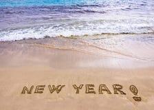 Nieuw jaar en uitroepteken dat in het zand wordt geschreven stock afbeelding