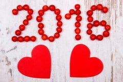 Nieuw jaar 2016 gemaakt van rode viburnum en rode houten harten op oude houten achtergrond Royalty-vrije Stock Afbeeldingen