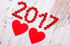 Nieuw jaar 2017 gemaakt van rode viburnum en rode houten harten op oude houten achtergrond Stock Foto