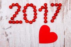 Nieuw jaar 2017 gemaakt van rode viburnum en rood houten hart op oude houten achtergrond Stock Foto