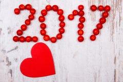 Nieuw jaar 2017 gemaakt van rode viburnum en rood houten hart op oude houten achtergrond Stock Afbeelding