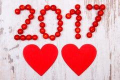 Nieuw jaar 2017 gemaakt van rode viburnum en rood houten hart op oude houten achtergrond Royalty-vrije Stock Fotografie
