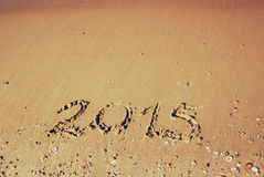 Nieuw jaar 2015 geschreven op zandig strand retro gefiltreerd beeld Royalty-vrije Stock Afbeeldingen