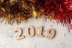 Nieuw jaar 2019 Kerstmis Vakantie Samenstelling met nummer 2019 en Kerstmisslingers op een lichte achtergrond Mening van hierbove stock foto