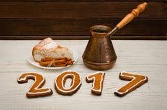 Nieuw jaar`s concept Het cijfer in 2017 van peperkoek, potten en appeltaart met kaneel op houten lijst Stock Foto