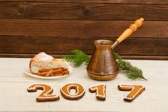 Nieuw jaar`s concept Het cijfer in 2017 van peperkoek, potten en appeltaart met kaneel op houten lijst Royalty-vrije Stock Fotografie
