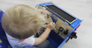 Nieuw onderwijsstuk speelgoed Montessori Een kleine jongen speelt pret in de auto stock videobeelden