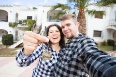 Nieuw onroerende goederen Huis, en bewegend concept - Grappige jonge paar het tonen sleutels van nieuw huis stock foto