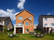Nieuw plattelandshuisje met lijst en stoelen op gazon Royalty-vrije Stock Foto's
