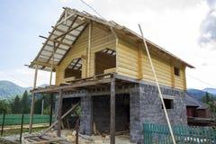 Nieuw plattelandshuisje van natuurlijke materialen in aanbouw op de achtergrond van de bergenmening Houten muren en dak op hoge s stock foto's
