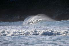 NIEUW ZEELAND, CHRISTCHURCH - JULI 2016: Surfer bij het surfen op reusachtige oceaangolven Extreme sporten in Nieuw Zeeland De va stock foto's