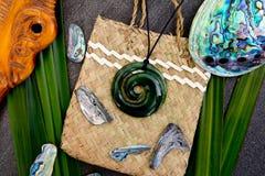 Nieuw Zeeland - Maori als thema gehade voorwerpen - jadetegenhanger met houten me stock foto's