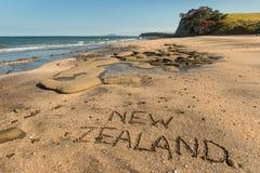 Nieuw Zeeland met de hand geschreven in zand Stock Afbeeldingen
