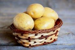 Nieuwe aardappels Gehele nieuwe aardappel in een rieten die mand op een uitstekende houten lijst wordt geïsoleerd close-up Royalty-vrije Stock Foto
