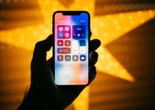 Nieuwe Apple-iPhone tegen blauw defocused ster die controle kenmerken Royalty-vrije Stock Afbeeldingen