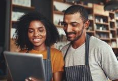 Nieuwe bedrijfseigenaars die tablet in koffie gebruiken royalty-vrije stock foto's