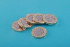 Nieuwe Brits, het UK één pondmuntstukken op een blauwe achtergrond Royalty-vrije Stock Afbeeldingen