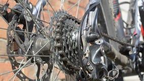 Nieuwe cassette met toestellen en ketting op het achterwiel van de oude grijze fiets stock footage