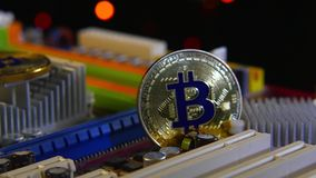 Nieuwe crypto munt, gouden muntstukken bitcoin op motherboard stock videobeelden