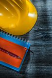 Nieuwe de veiligheid van de notitieboekjespen de bouwhelm op houten raad royalty-vrije stock fotografie
