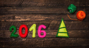 Nieuwe die jaar 2016 achtergrond met Kerstmisstuk speelgoed van gevoeld op donkere roest wordt gemaakt Stock Foto's