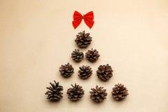 Nieuwe die jaarboom bij ecostijl wordt gemaakt van pinecones en rode boog Stock Foto