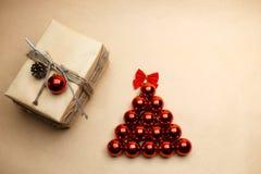 Nieuwe die jaarboom met gift bij ecostijl wordt ingepakt met rode bellen en pinecone Stock Afbeeldingen