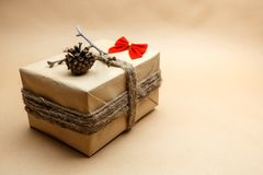 Nieuwe die jaargift bij ecostijl wordt ingepakt met rode bellen, pinecones en boog Royalty-vrije Stock Afbeelding