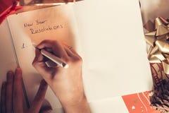 Nieuwe die jaarresoluties met een hand worden geschreven over notitieboekje met nieuwe ye Stock Fotografie